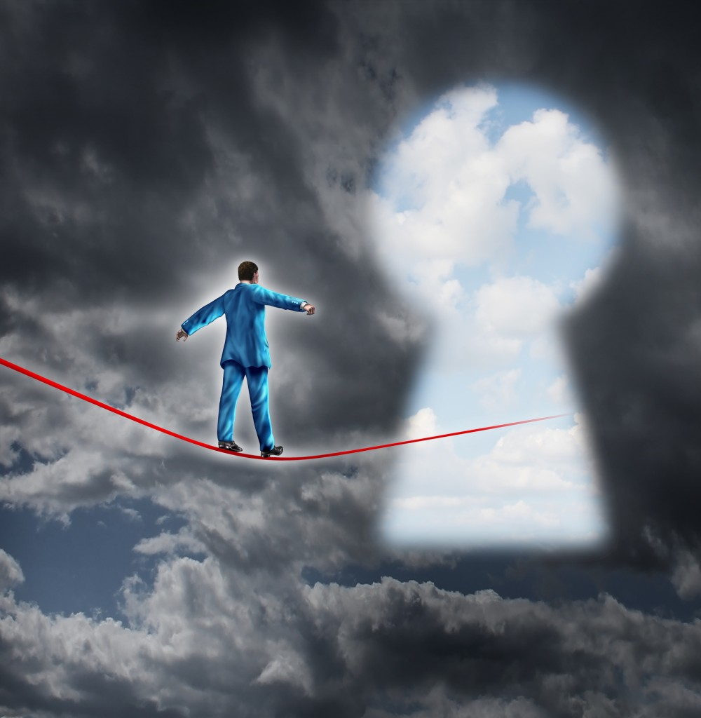 Risk and opportunity business concept with a businessman on a dark storm background walking on a red tight rope that is leading into a key hole shaped as a bright sky for financial freedom and career success.